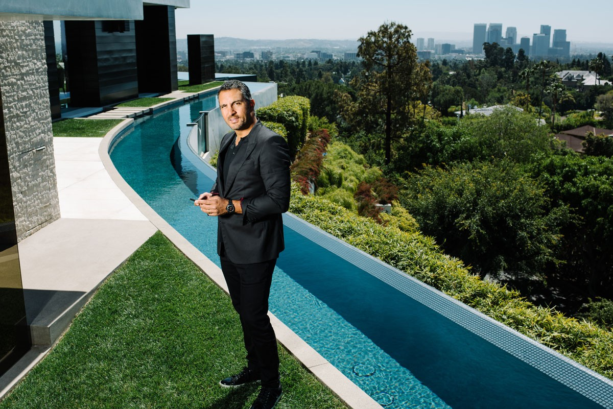 Mauricio Umansky stands on his property at Beverly Hills with California on the backdrop. He looks well groomed in his black suit.