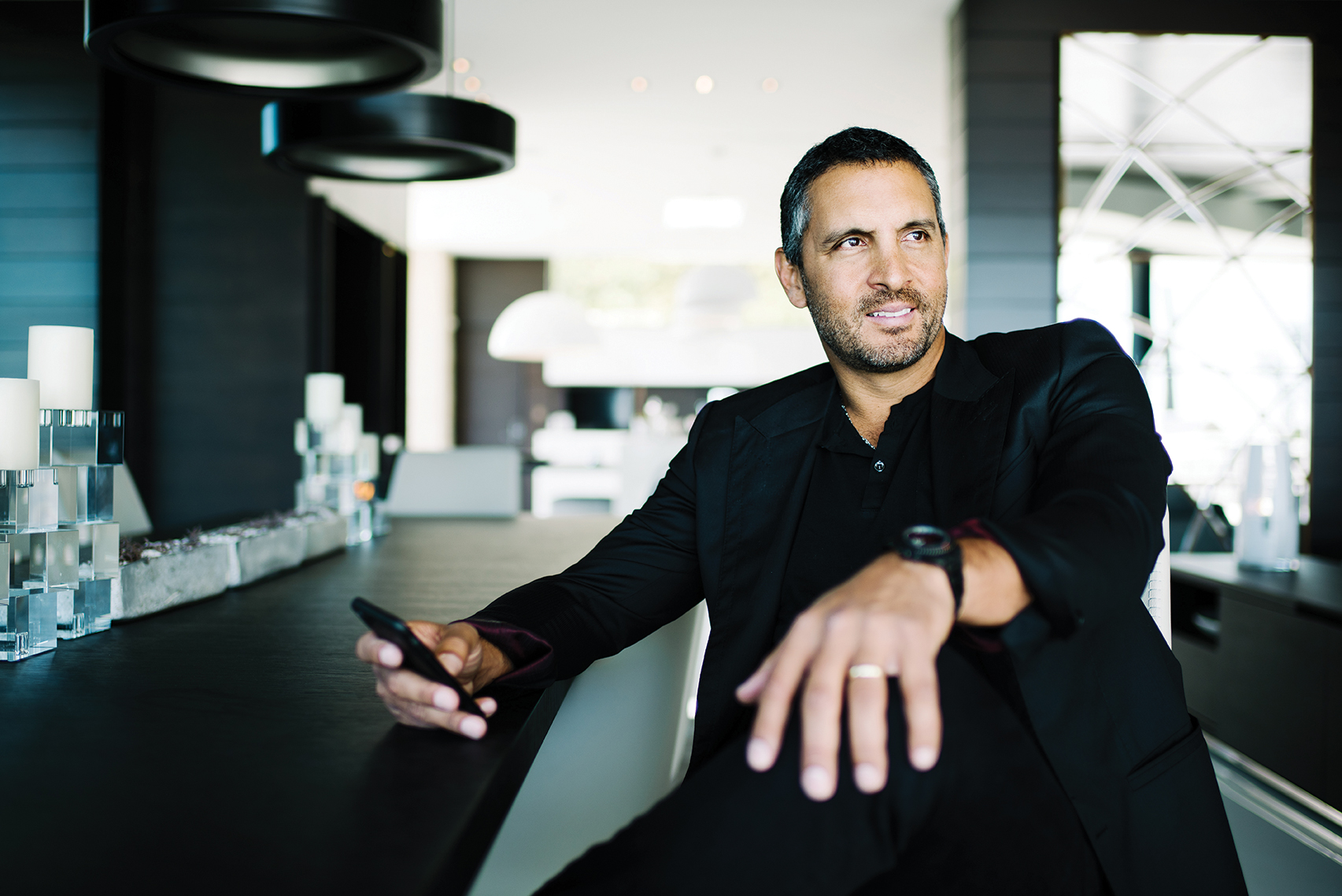 Mauricio Umansky looks breathtaking in his black suit. He is sitting in a well-furnished room.