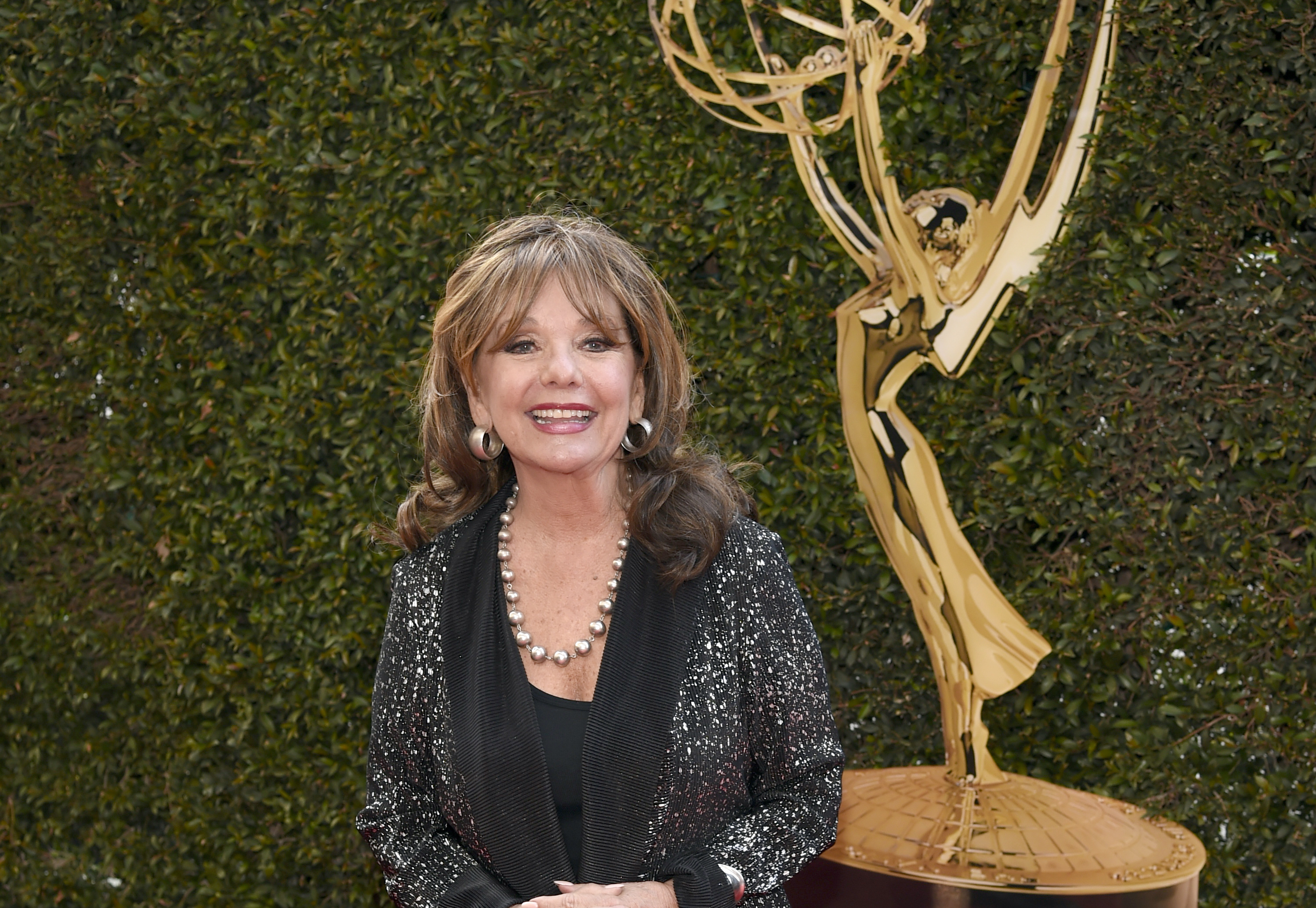 Dawn Wells smiling for a picture infront of a big Emmy statue