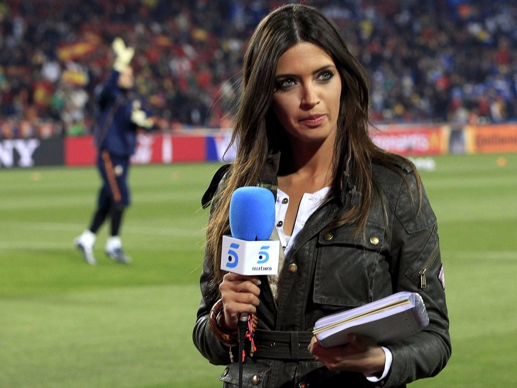 Sara Carbonero on the field holding a mike and reporting for Telecinco