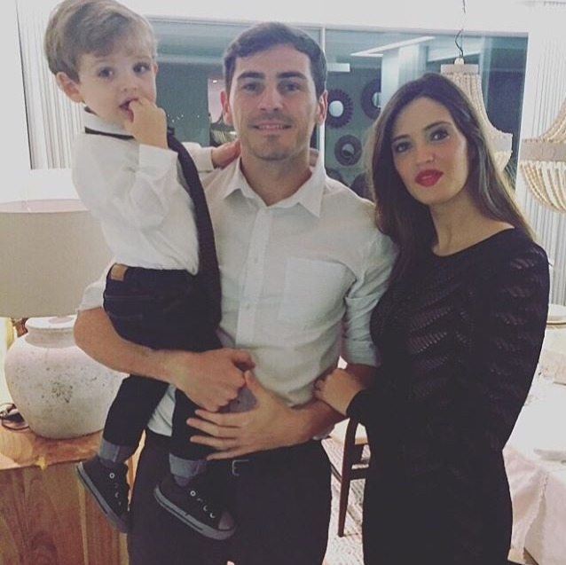 Sara Carbonero is looking at camera standing close to husband Iker Casillas while he is holding son, Martin