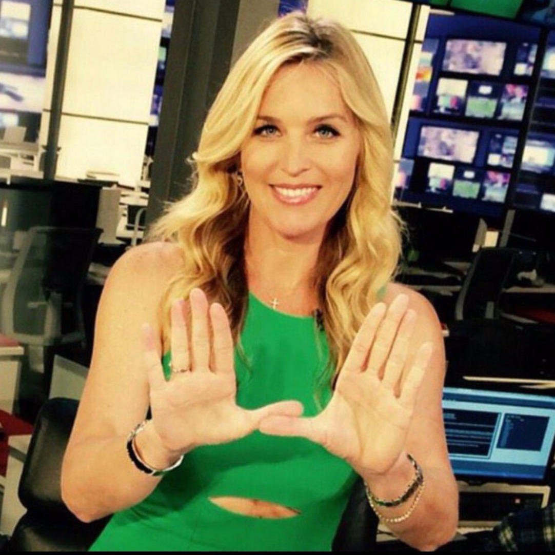 KCBS sportscaster Jill Arrington shows a symbol of University of Miami Hurricanes Athletics on College Colors Day