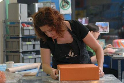 Sofia Rodriguez decorating cake at Charm City Cakes