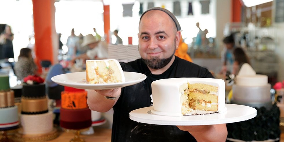 Duff Goldman holding the plates of cakes on his both hands