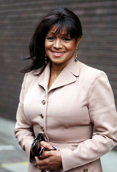 Rebbie Jackson is wearing a beautiful coat. She is holding a sunglass on her hand and is smiling for the camera.