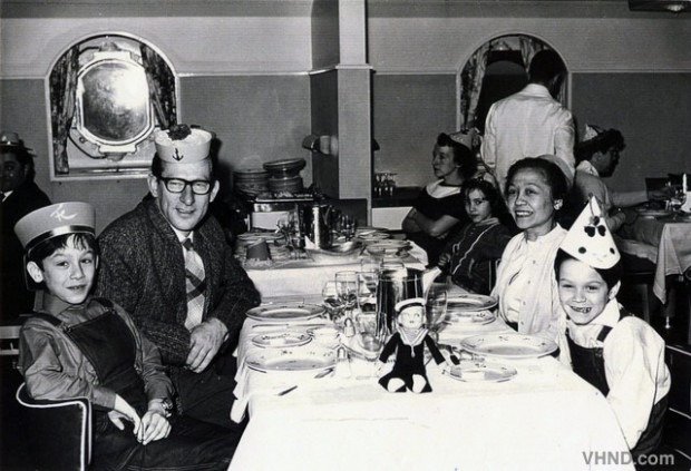 Eddie is sitting at a table with his father, mother and older brother, on a ship to America.