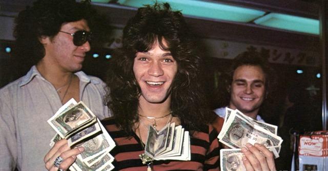 Eddie Van Halen, from his heydays, holding bundles of cash in his hand, smiling, flaunting his rock hair.