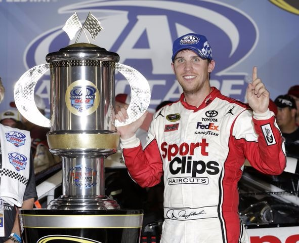 Denny Hamlin is touching Advocare 500 trophy with one hand. He is pointing up the index finger of his other hand.
