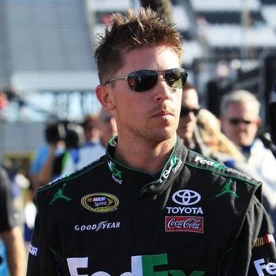 Denny Hamlin is looking sideways. He has spiky hair and is wearing sunglasses.