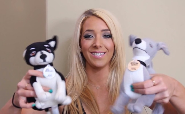 Jenna Marbles is holding the toy dogs that look like her real dogs Marbles and Kermit.