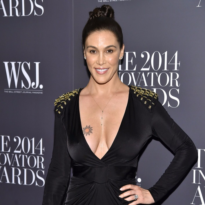 Nicole Young poses in a black dress during the Innovator of the Year Awards 2014. She is wearing a black dress with long v-neck cut. She has a tattoo on the right side of her chest.