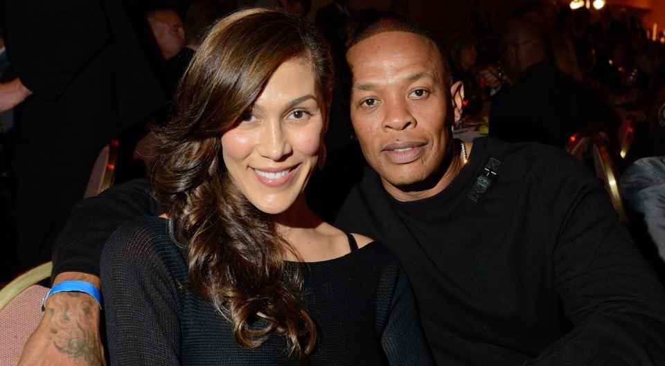Nicole Young and Dr. Dre attend a party together. Dr. Dre is cosying up to his wife as they pose for a photo.