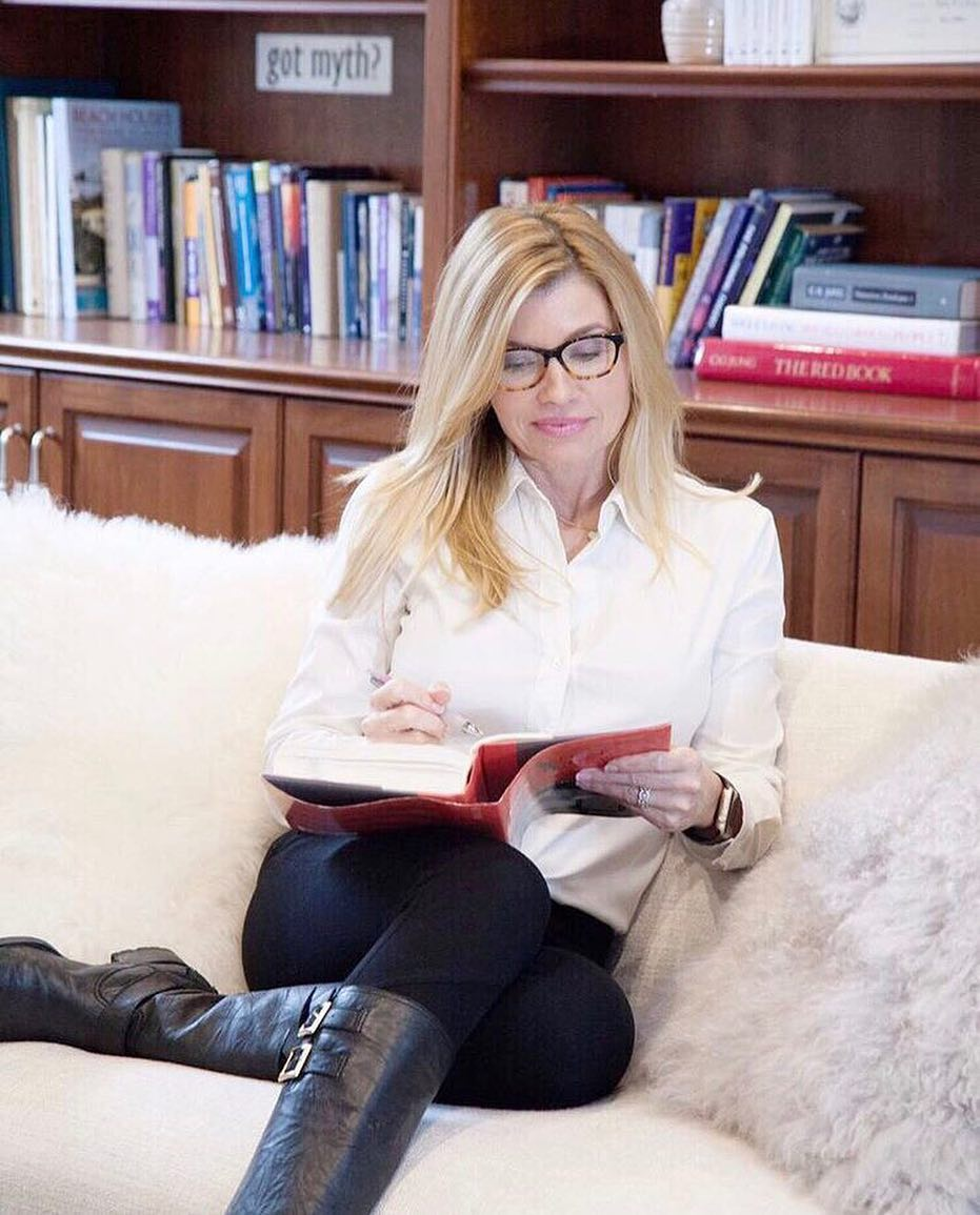 Nadine Caridi is sitting in a couch and has a book in her hand