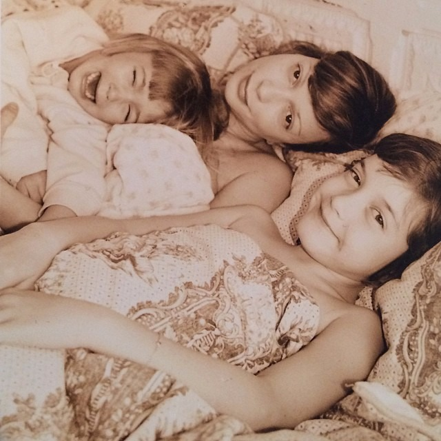 Kennya Baldwin is lying in the bed with her two daughters Alaia and Hailey. The picture of Kennya is taken during her young age. Hailey is crying while Kennya and Alaia is smiling.