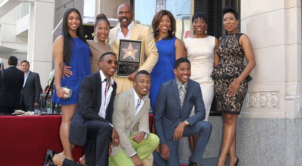 Steve Harvey poses with a star in his hand along with his family