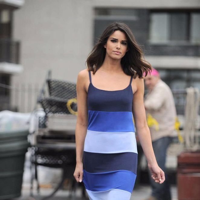 Jennifer Lahmers is posing on the road. She is wearing a dress with different shades of blue color and she has a lob cut. Hot Jennifer has a model like looks.