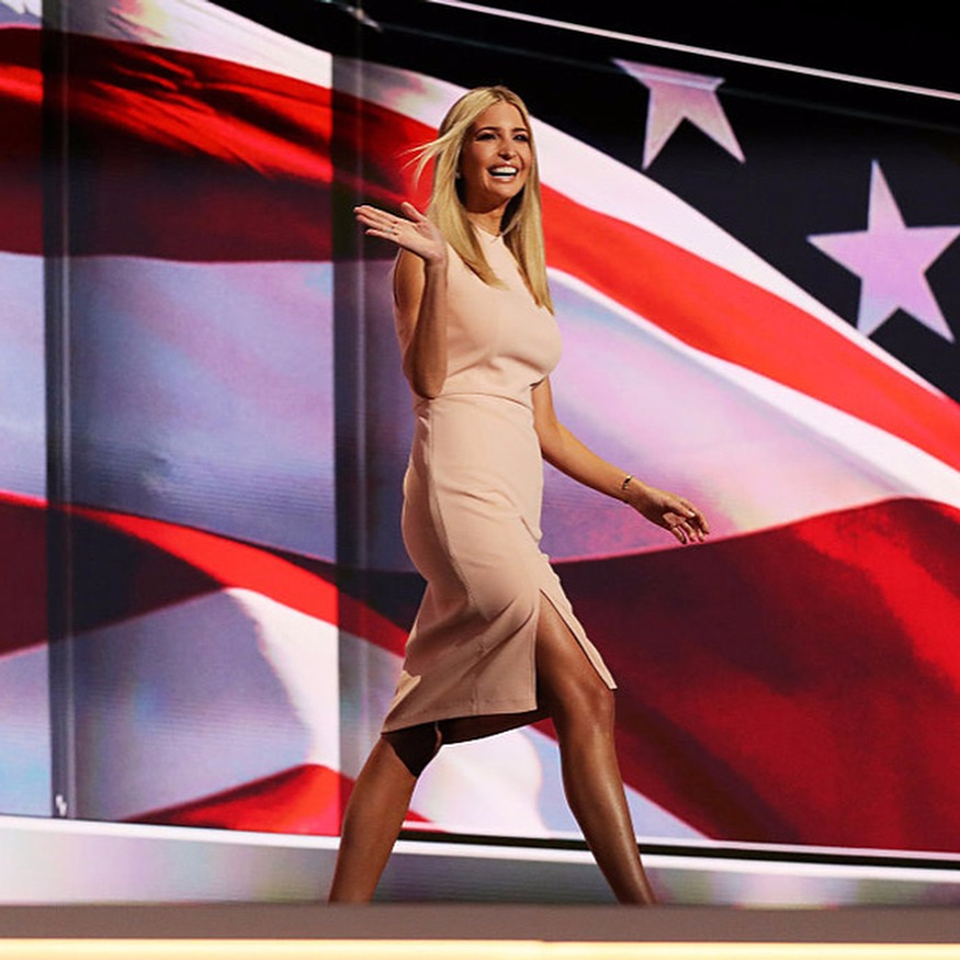 Ivanka Trump walking as she waves to fans, there's a big screen with a waving American flag in the background
