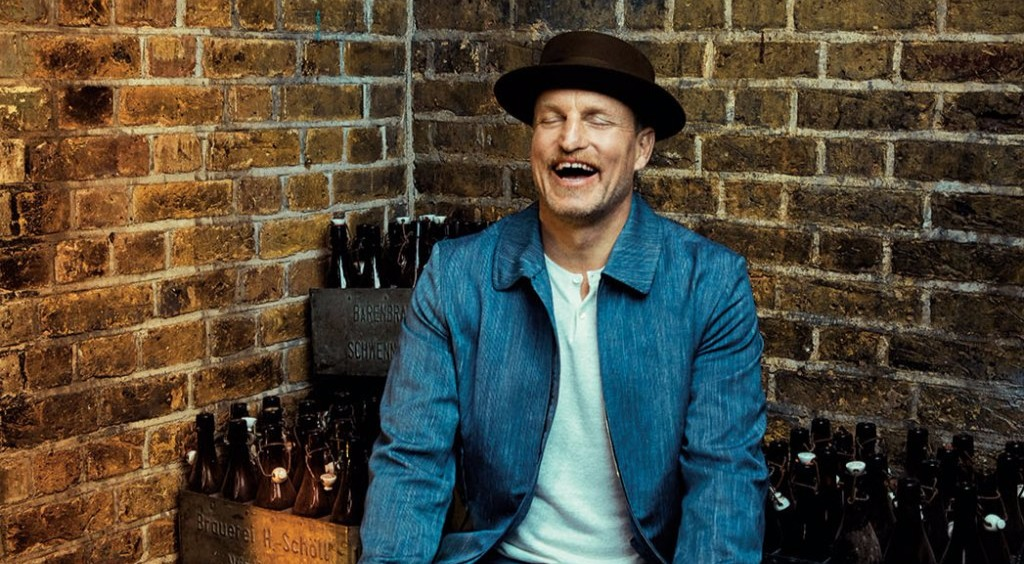 Woody Harrelson smiling widely, he's wearing a hat and there's a brick wall behind him