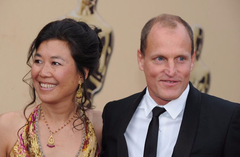 Young Woody Harrelson is looking sideways at wife Laura Louie