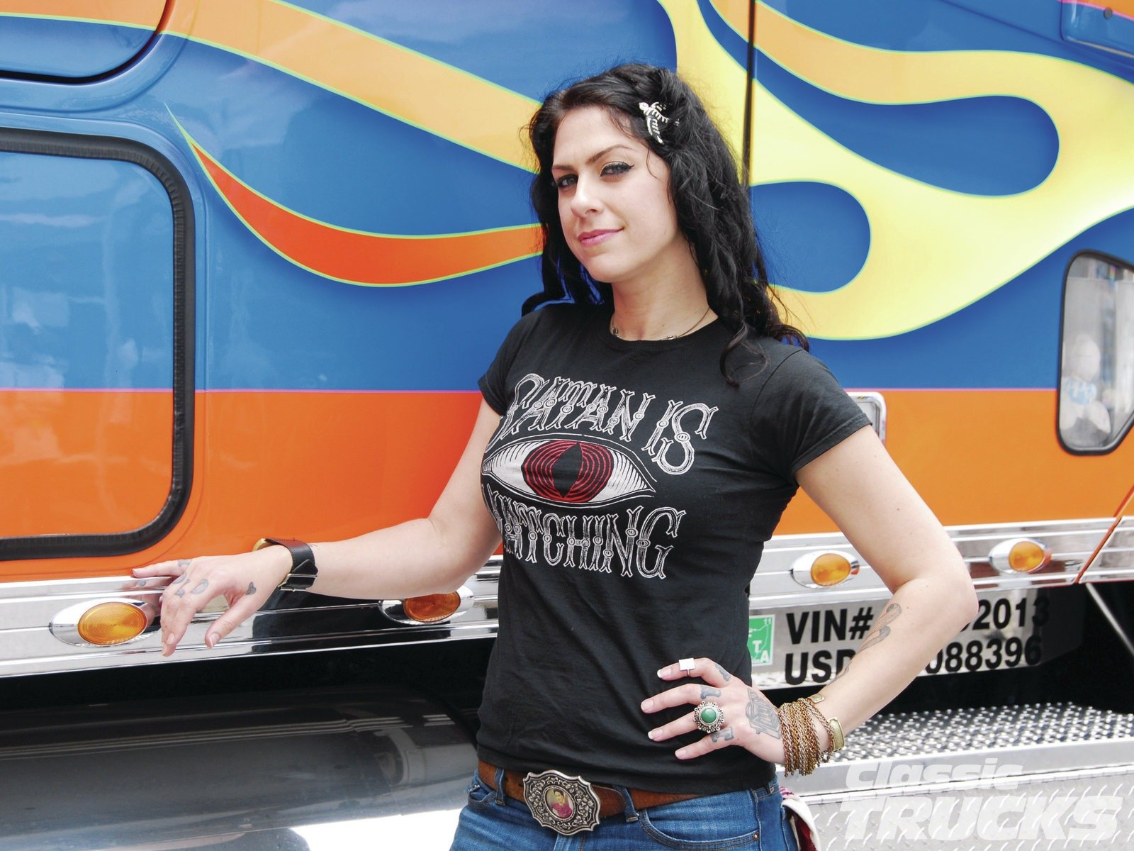 American Pickers' Danielle Colby is smiling at the camera. She is keeping one hand in her waist and the other hand is on the bus