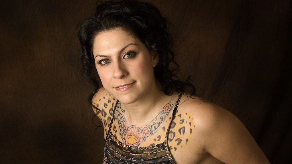 Danielle Colby is flaunting her tattoo. She is wearing thin-stripped dress. She is posing for the camera effortlessly.