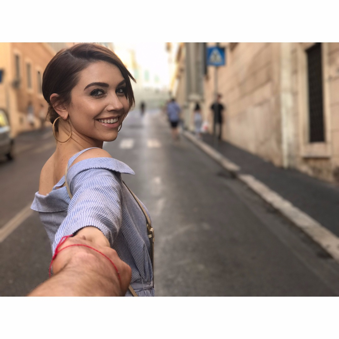 Jenna Johnson holds a hand while taking a picture in Italy