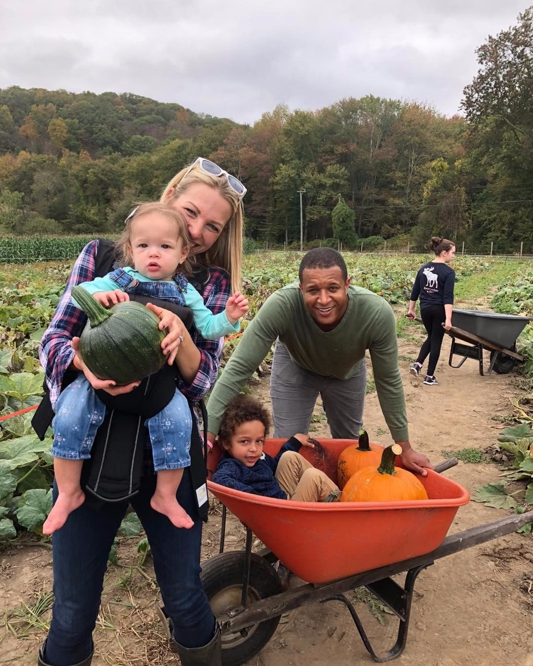 Craig Melvin's day out  with his family. They hold two pumpkins and a gourd. They are having fun in a pumpkin field.
