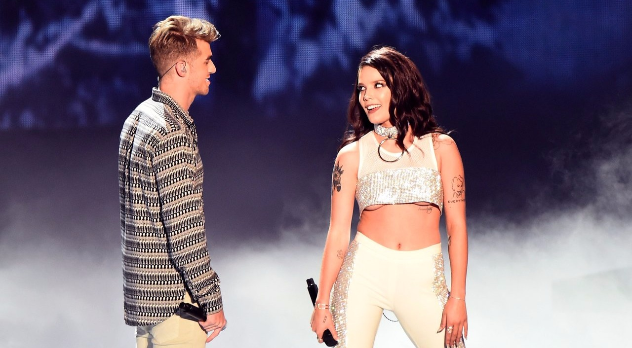 Andrew Taggart and Halsey holding mics and looking at each other while performing on the stage of 2016 MTV VMAs