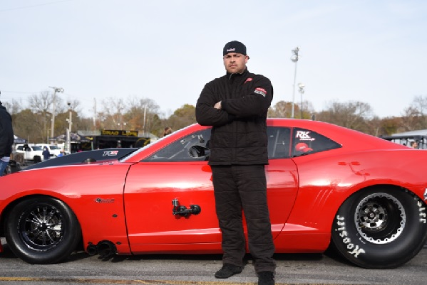 Ryan Martin standing in front of his red shiny Fireball Camaro with his arms folded.