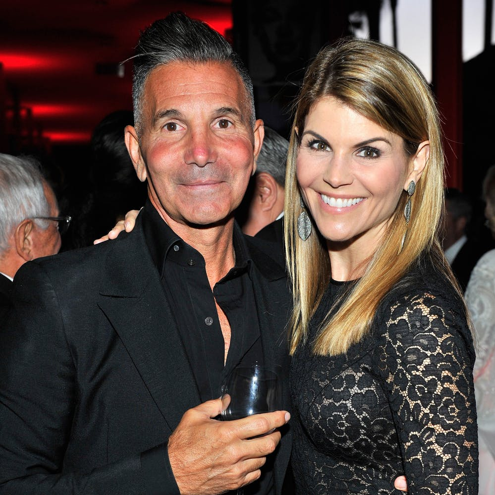 Lori Loughlin and husband, Mossimo Glannulli shares a smile as they pose