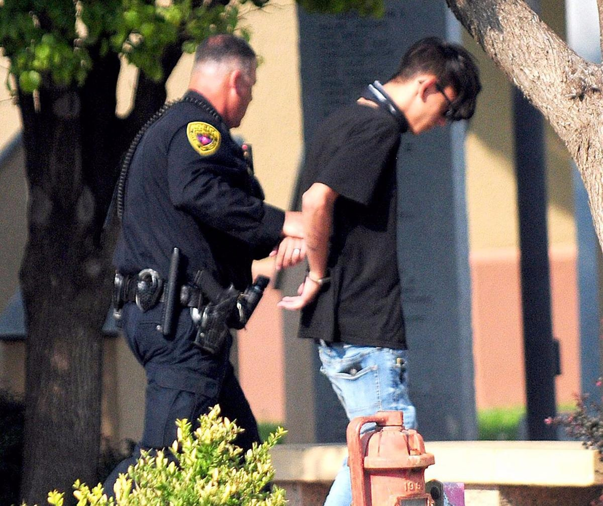 A police officer is holding the hand of the suspect of New Mexico library shooting