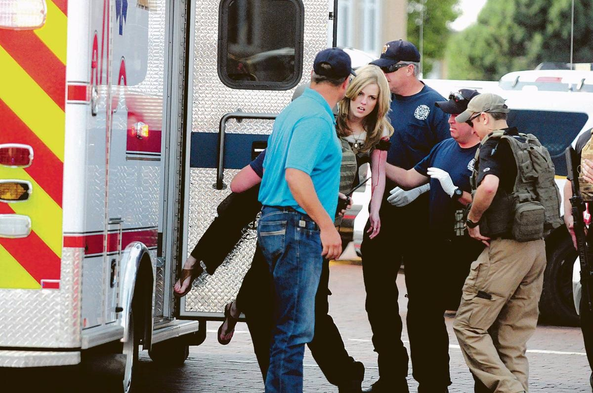An injured woman is being carried by a man in attempt to get her inside the ambulance.