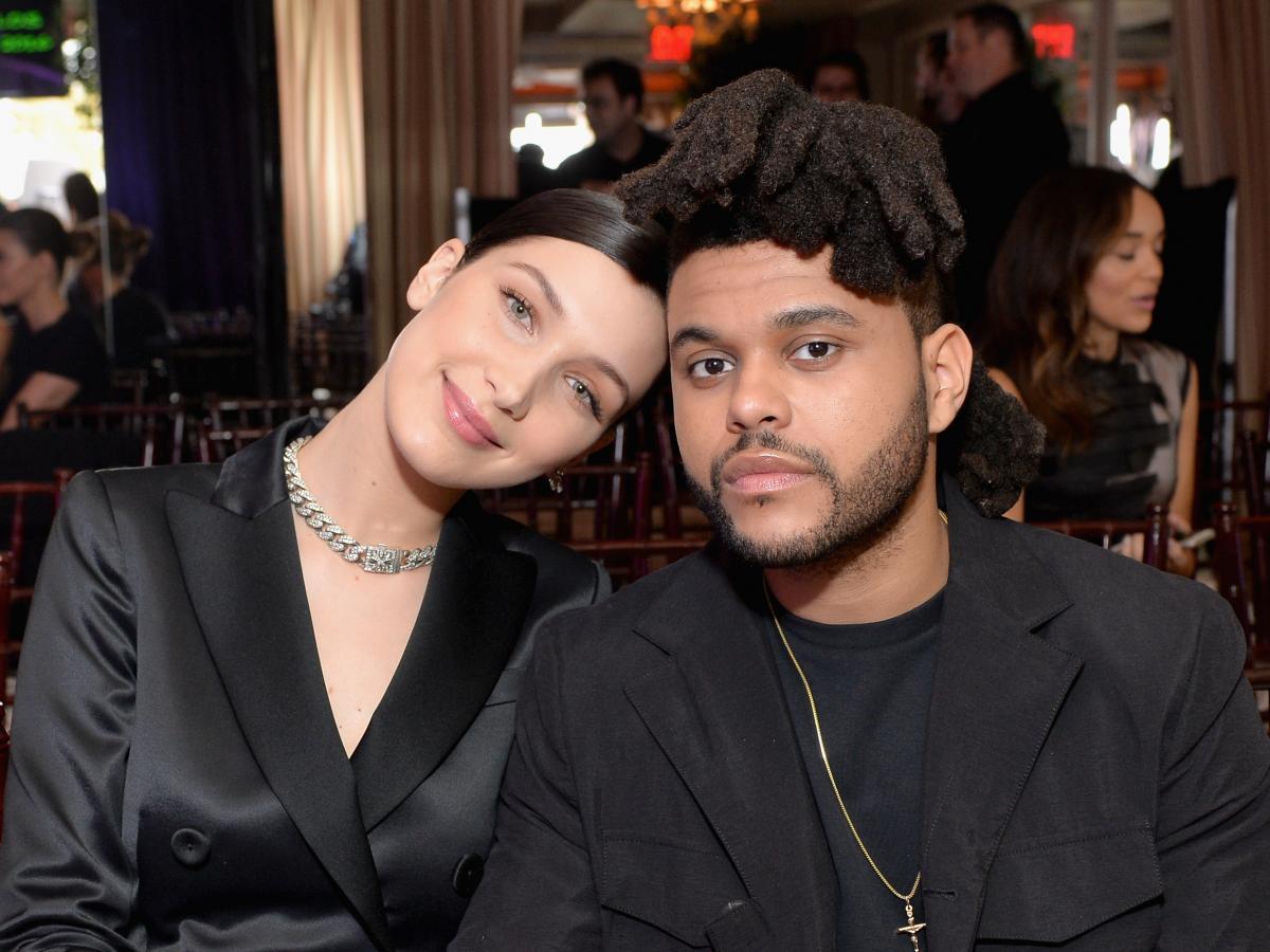 Bella Hadid is tilting her head toeards  the Weeknd