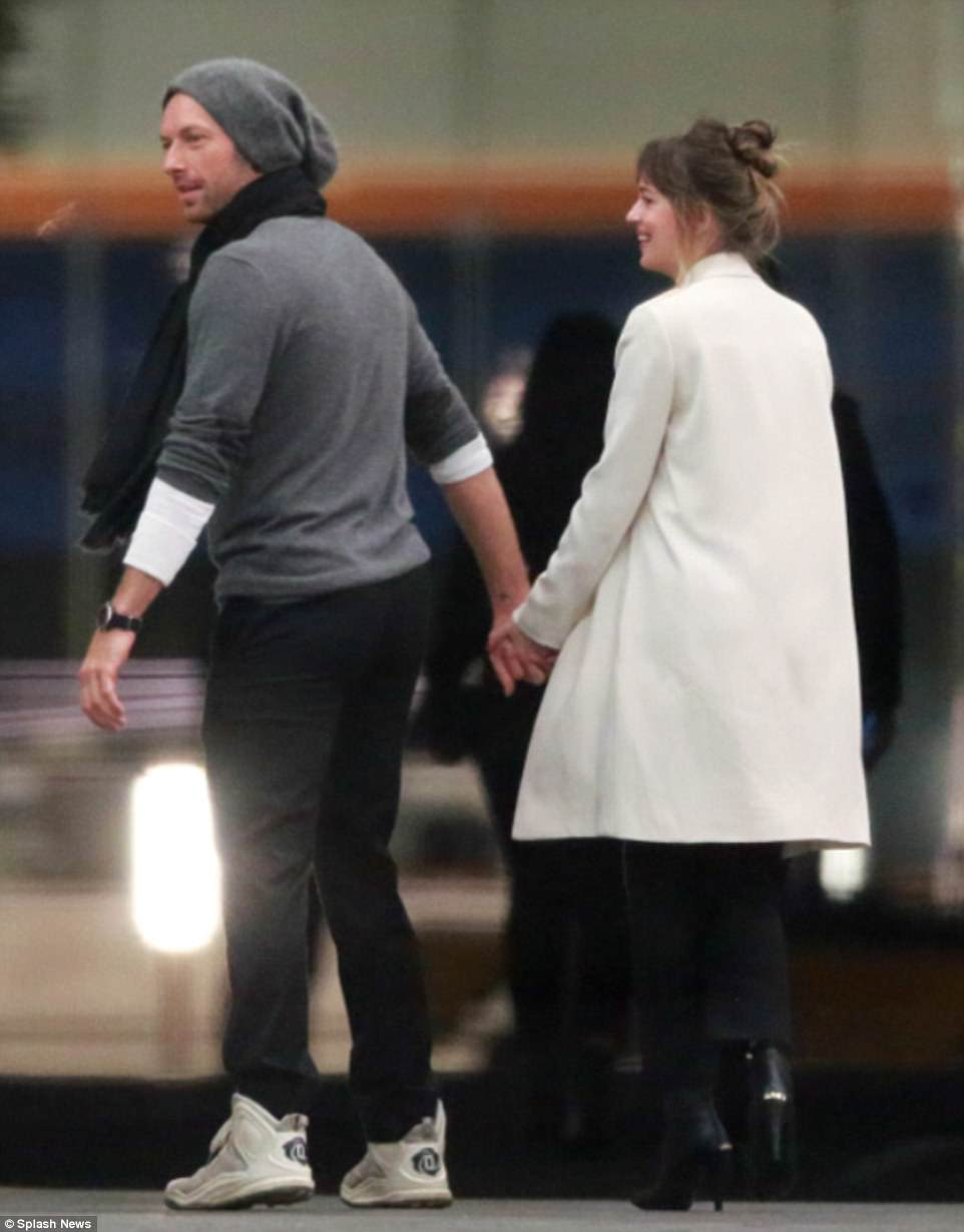 Chris Martin is holding the hand of Dakota Johnson