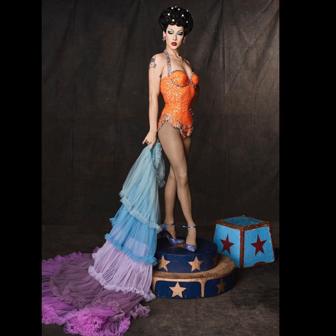 Violet Chachki is standing wearing orange dress