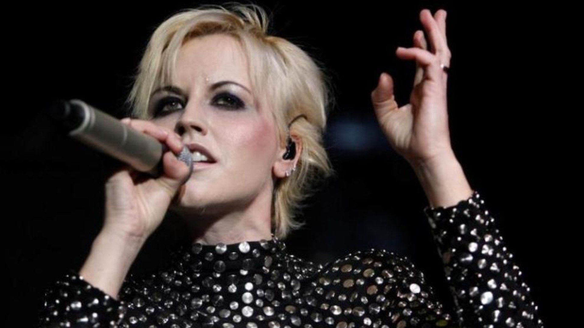 Dolores O'Riordan holding a mic in her right hand