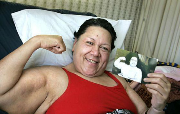 Emily Dole flexing her muscle and holding a young  picture of her own
