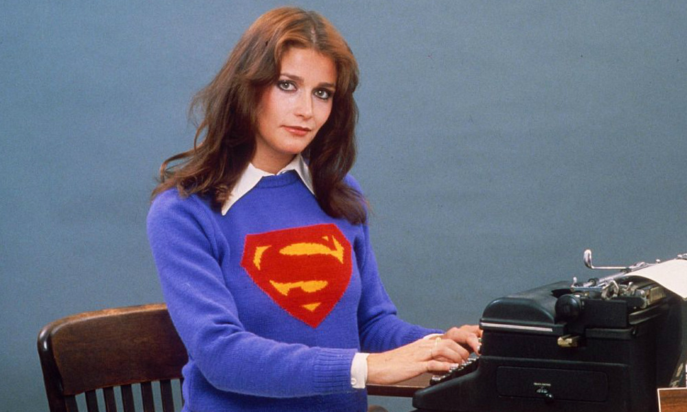 Margot Kidder wearing a sweater with a superman logo on it