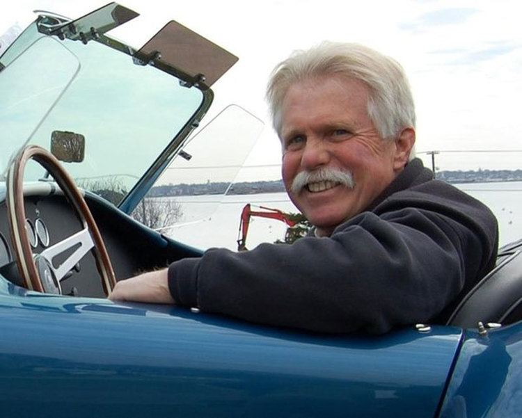 Wayne Carini driving a vintage car with a wide smile on his face