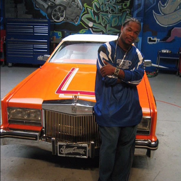 Rapper Xzibit standing in front of the classic orange car