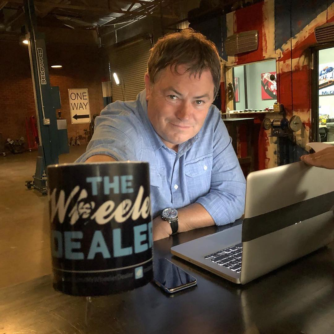 "Mike Brewer holding a mug with a letter ""THE Wheeler DEALERS"" imprinted on it"