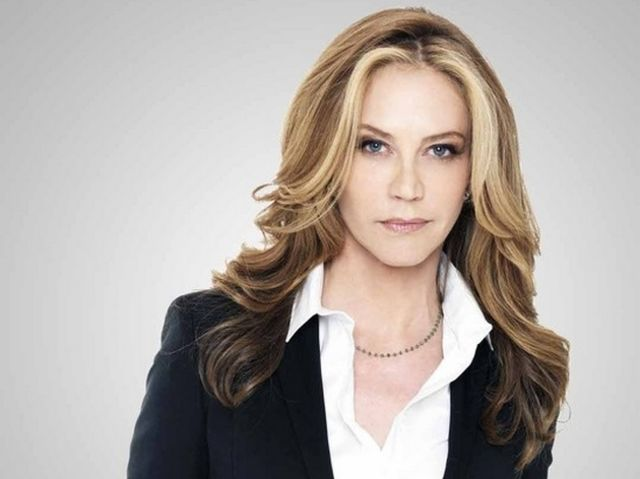 Ally Walker wearing white shirt and black coat