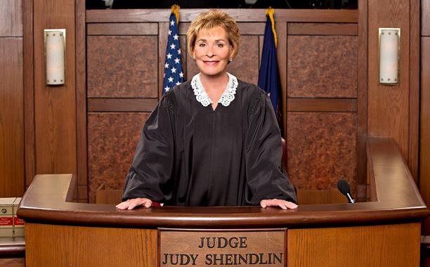 Judy Sheindlin standing at the podium of judging panel