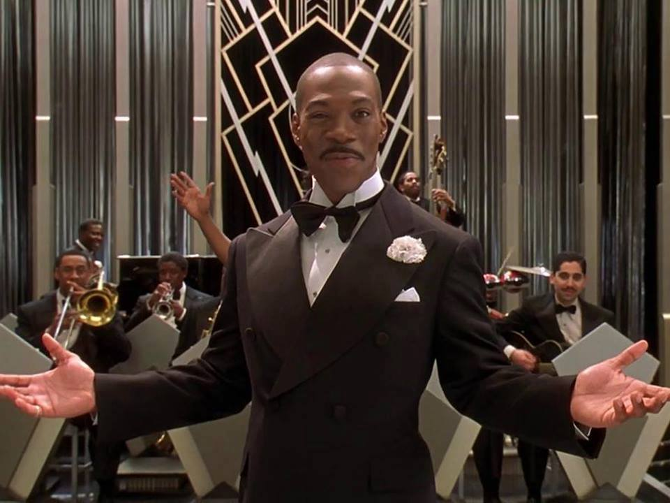 Eddie Murphy standing in front of the orchestra with his arms open