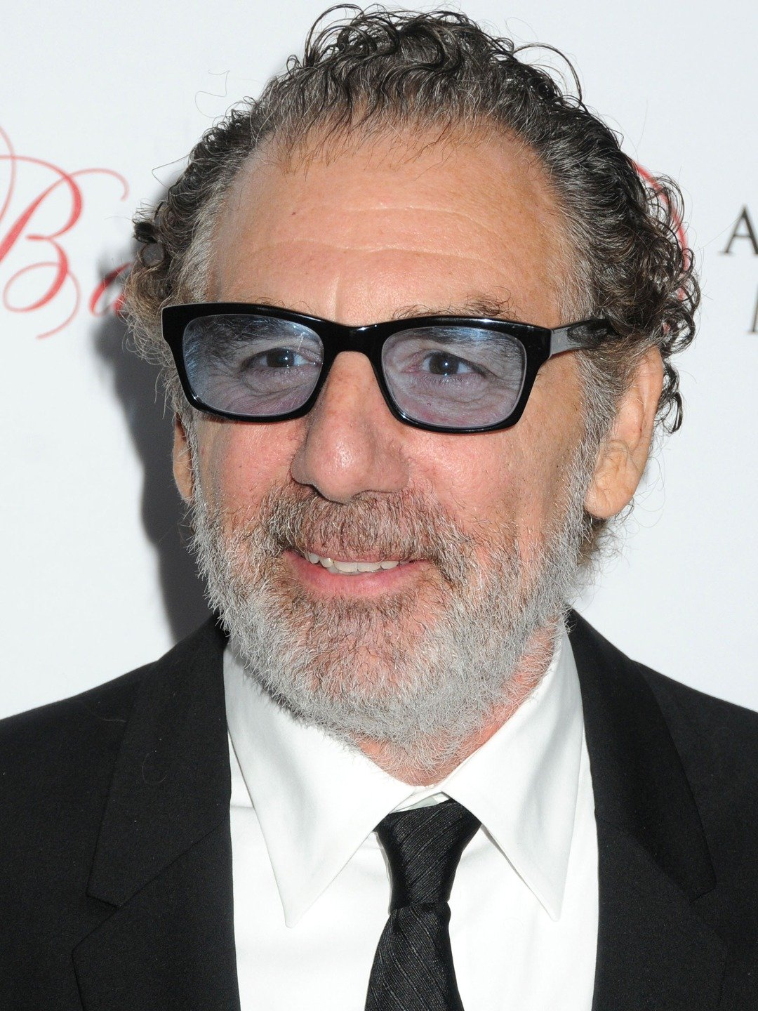 Michael Richards  wearing white shirt, black tie and suit