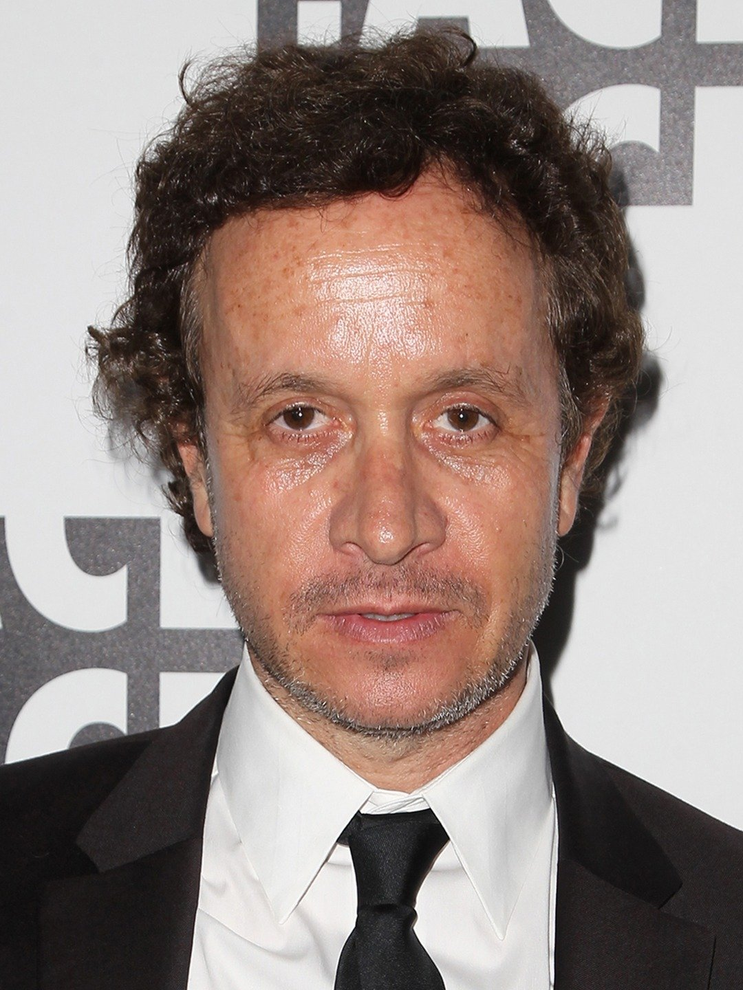 Pauly Shore attending an event all dressed up in white shirt, black tie and suit