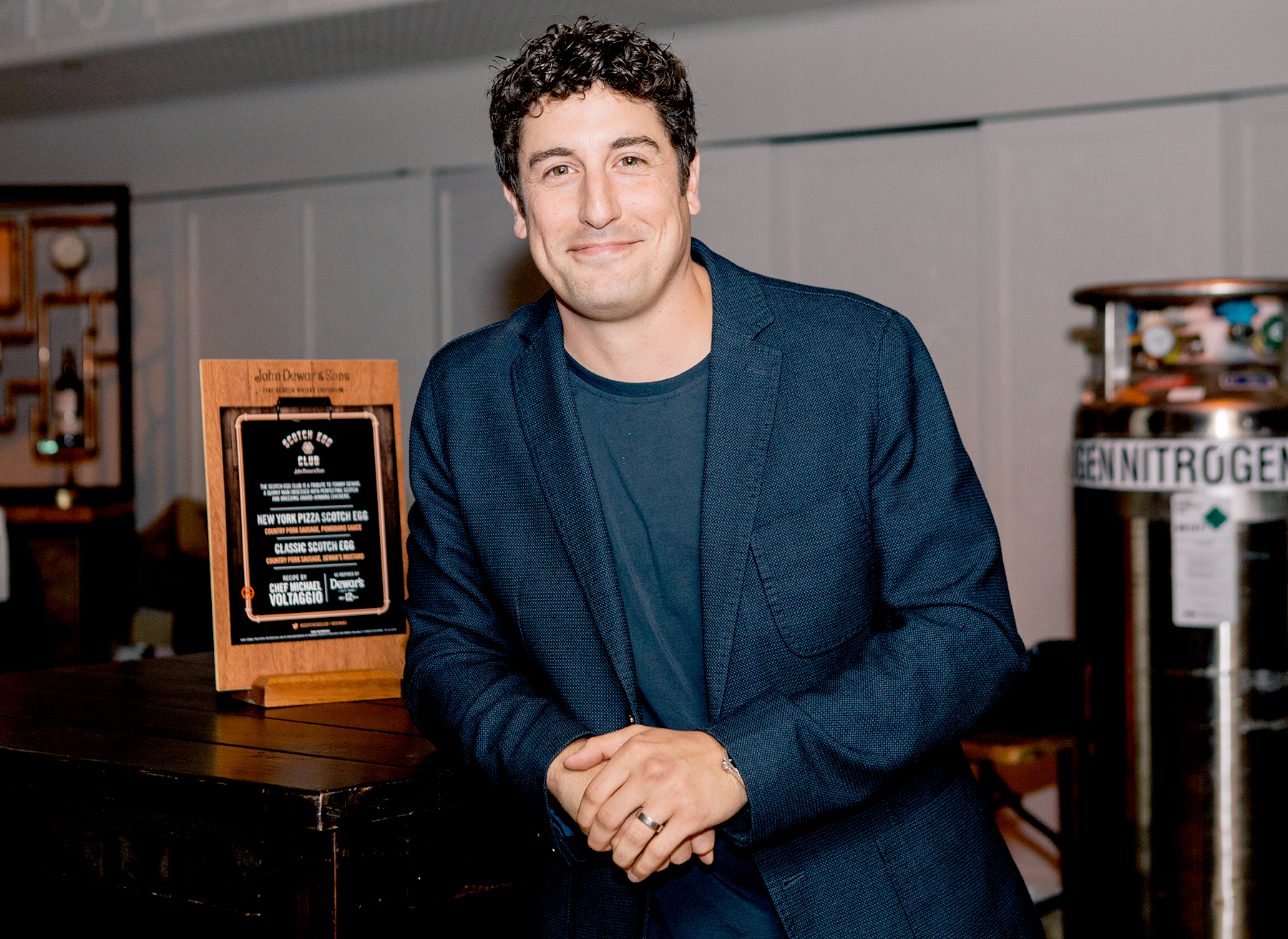 Jason Biggs leaning a table with a subtle smile in his face