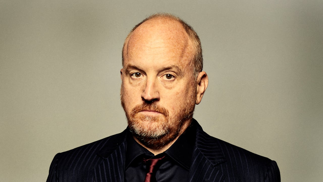 Louis CK with a bald head and serious look on his face