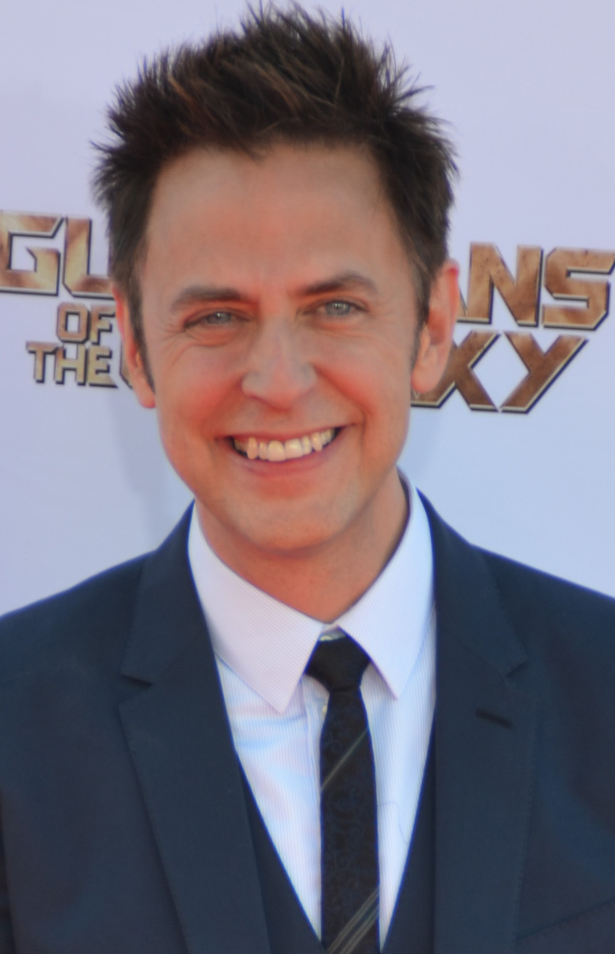 James Gunn is wearing a white shirt and a black suit and tie