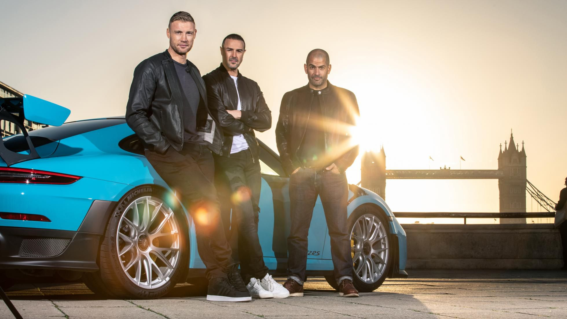 New hosts of the Top Gear alongside a blue car. All three are wearing leather jackets and jeans